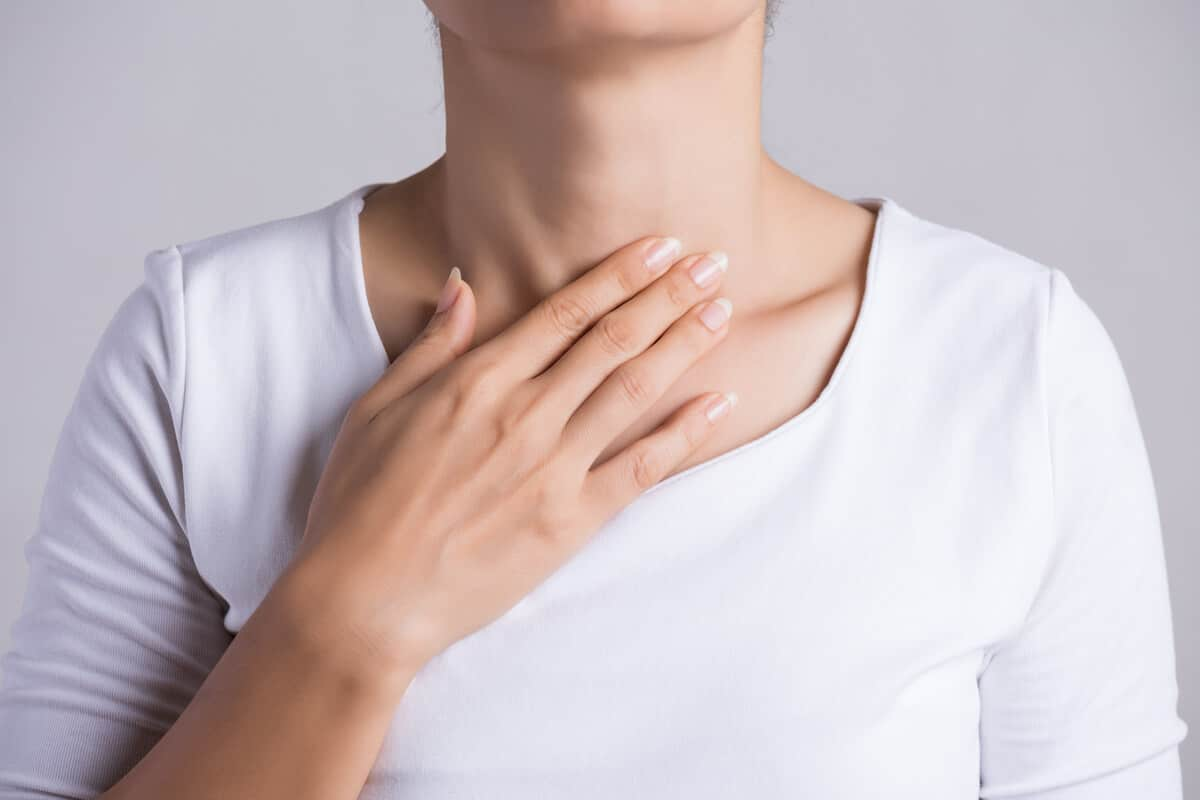 hypothyroidism vs. hyperthyroidism person holding throat